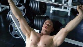 Homem muscular descamisado que faz o exercício da imprensa de banco do barbell no gym vídeos de arquivo