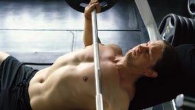 Homem muscular descamisado que faz o exercício da imprensa de banco do barbell no gym video estoque