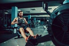 Homem muscular do ajuste que usa a máquina de enfileiramento no gym imagem de stock royalty free