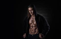 Homem muscular dos esportes após pesos que treina sobre o fundo preto fotos de stock