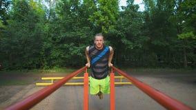 Homem muscular durante seu exercício no parque Mergulhos, caixa do exercício e tríceps video estoque