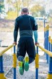 Homem muscular em barras paralelas imagens de stock