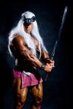 Homem muscular em uma imagem de um bárbaro com uma espada aumentada. Fotos de Stock
