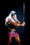 Homem muscular em uma imagem de um bárbaro com uma espada aumentada. Imagem de Stock