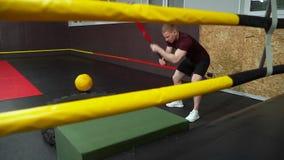 Homem muscular forte que bate um malho no pneu no gym filme