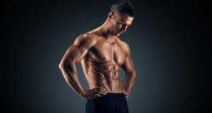 Homem muscular no estúdio no fundo escuro Fotografia de Stock Royalty Free