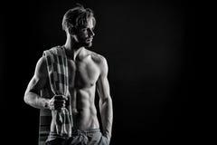 Homem muscular no fundo escuro com toalha Inquietação com seu corpo após o exercício duro Preto e branco, atleta para o magazin o Fotografia de Stock Royalty Free