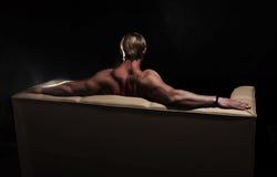 Homem muscular no sofá fotografia de stock royalty free