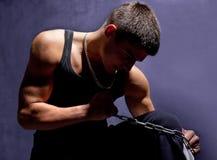 Homem muscular novo com uma corrente isolada na obscuridade Foto de Stock Royalty Free