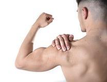 Homem muscular novo do esporte que guarda o ombro dorido na dor que toca na massagem no esforço do exercício Foto de Stock