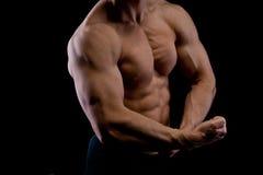 Homem muscular novo dos esportes no preto fotografia de stock royalty free