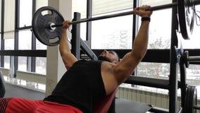 Homem muscular novo na imprensa de banco Trens do indivíduo no gym com um barbell video estoque