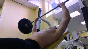 Homem muscular novo na imprensa de banco Trens do indivíduo no gym com um barbell filme