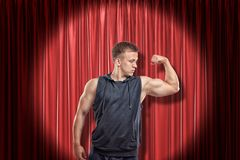 Homem muscular novo na roupa preta do esporte que mostra o bíceps esquerdo do braço no fundo vermelho das cortinas da fase foto de stock royalty free