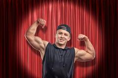 Homem muscular novo na roupa preta do esporte que sorri e que mostra o bíceps no fundo vermelho das cortinas da fase foto de stock royalty free