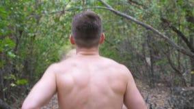 Homem muscular novo que corre ao longo da fuga no desportista irreconhecível da floresta adiantada do outono que corre ao longo d filme