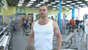 Homem muscular novo que faz o exercício com pesos no gym Retrato do halterofilista masculino no exercício do gym vídeos de arquivo