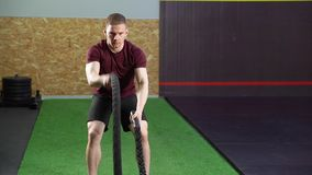 Homem muscular novo que faz o treinamento pesado da corda no gym vídeos de arquivo