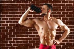 Homem muscular novo que mostra seus corpo e abanador perfeitos imagens de stock