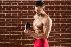 Homem muscular novo que mostra seus corpo e abanador perfeitos imagem de stock royalty free