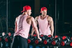 Homem muscular para fora no gym que está pesos próximos, uma camisa cor-de-rosa e o boné de beisebol vermelho Foto de Stock