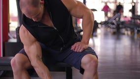 Homem muscular que aprecia o exercício no gym, orgulhoso de seus resultados, treinamento do halterofilista vídeos de arquivo