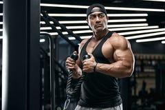 Homem muscular que dá certo no gym que faz exercícios para os bíceps Macho forte foto de stock royalty free
