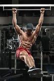 Homem muscular que dá certo no gym, fazendo exercícios de estômago em uma barra horizontal, Abs despido masculino forte do torso Fotografia de Stock Royalty Free
