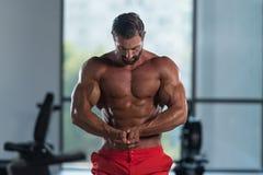 Homem muscular que dobra os músculos no gym imagem de stock royalty free