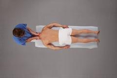 Homem muscular que está sendo feito massagens pelo terapeuta Foto de Stock