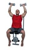 Homem muscular que exercita ao sentar-se na imprensa de banco fotos de stock royalty free