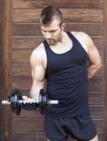 Homem muscular que exercita com peso no fundo de madeira. imagens de stock