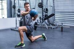 Homem muscular que faz exercícios da bola de medicina foto de stock