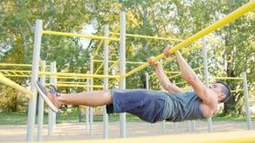 Homem muscular que faz exercícios na barra horizontal filme