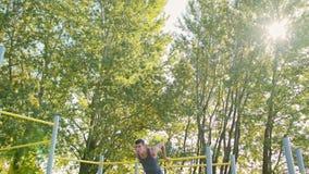 Homem muscular que faz exercícios na barra horizontal video estoque