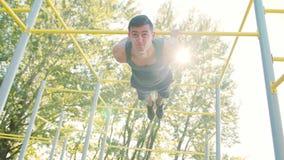 Homem muscular que faz exercícios na barra horizontal vídeos de arquivo