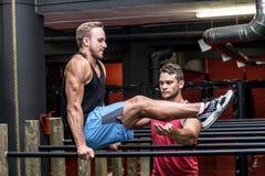 Homem muscular que faz exercícios na barra paralela Fotografia de Stock Royalty Free
