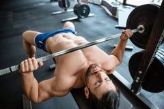 Homem muscular que faz a imprensa de banco imagem de stock