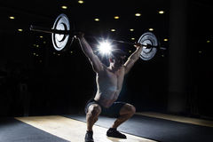 Homem muscular que faz o exercício do crossfit no gym imagem de stock