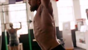 Homem muscular que faz o exercício pesado poderoso vídeos de arquivo