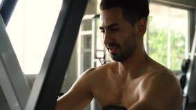 Homem muscular que faz o exercício traseiro assentado da máquina da fileira no gym vídeos de arquivo
