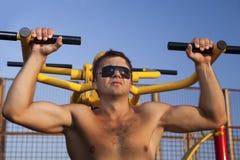 Homem muscular que faz o weightlifting imagem de stock