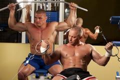 Homem muscular que faz o weightlifting na ginástica Imagem de Stock