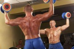 Homem muscular que faz o weightlifting na ginástica Fotos de Stock