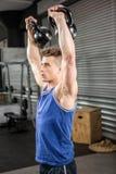 Homem muscular que levanta kettlebells pesados Fotografia de Stock