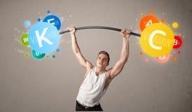 Homem muscular que levanta pesos coloridos da vitamina Fotografia de Stock
