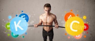 Homem muscular que levanta pesos coloridos da vitamina Foto de Stock Royalty Free