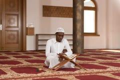 Homem muçulmano africano que lê o Alcorão islâmico santamente do livro Fotos de Stock