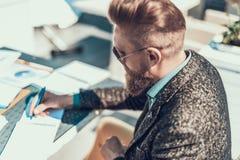 Homem não barbeado sereno que faz anotações no caderno fotos de stock royalty free