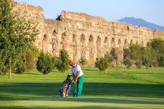 Homem não identificado que joga o golfe no campo de golfe ao lado de Roman Aqueduct antigo foto de stock